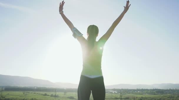 Mladý sportovní ženy stojící na okraji útesu, pozvedá ruce a vyskočí na nejvyšší hoře při západu slunce. Šťastná dívka těší úspěch a ohromující zobrazení