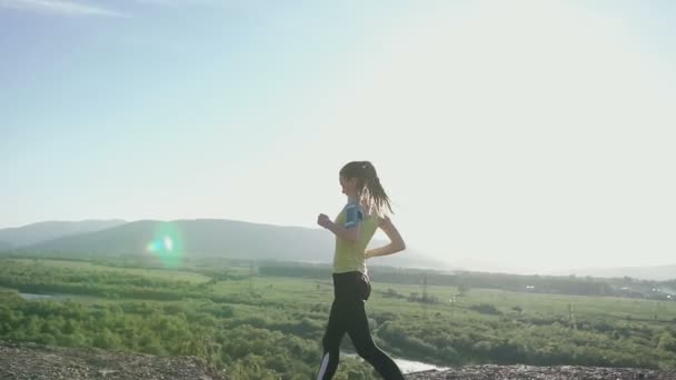 Athletic Caucasian girl running and listening to music at headphone on smartphone at the outdoor on the top mountain at sunset. Athletic girl makes a jog in the mountains while listening to music