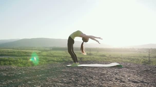 Aranyos alkalmas fiatal nő, ezzel a bemelegítés a természet stretching. Sport-fitnesz. Jóga, torna. Rugalmasság a képzés gyakorolja. Ritmikus gimnasztika lány teszi a nyújtás a bemelegítés a parkban szabadtéri