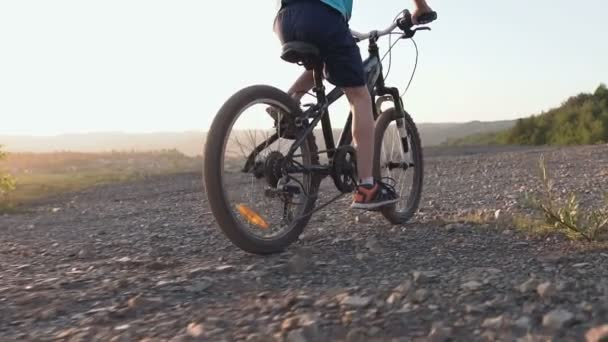 Rear view of a black mountain bike on which the guy rides for a walk 8-9 years. A child who rides a bicycle in the hills area at sunset in summer