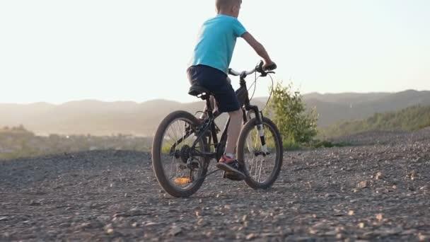 Zadní pohled na chlapce, který jezdí černé kolo v hornaté oblasti. Dítě, jízda na kole. Mladík na kole na horské silnici v předměstí v západu slunce v létě