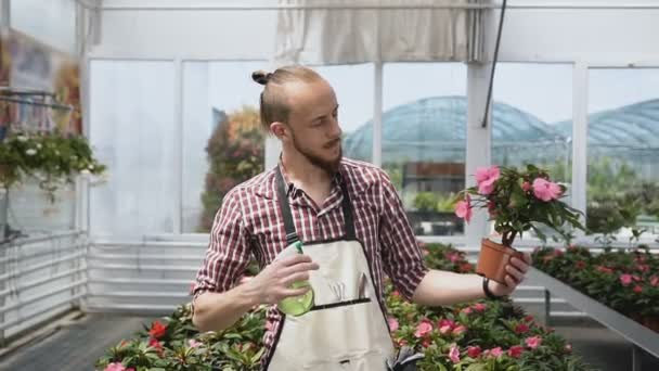 A young guy is a gardener in mittens and a garden apron, smiling and look on the camera. Large greenhouse of ornamental plants and flowers.