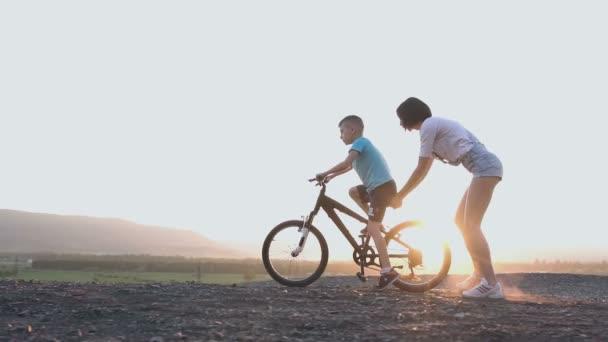 Mladá matka učí svého syna do jízdy na kole na letní západ slunce nebo východu slunce. Žena má kolo, na kterém její syn se naučí jezdit příjemnou rodinnou dovolenou, jízda na kole
