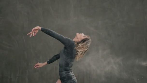 Krásné výrazné baletky v černém obleku tělo tancuje ve studiu v oblacích kouře nebo bílého prášku. Hezká mladá žena tanečnice oblečené v těle černé tričko, šortky a baletka boty