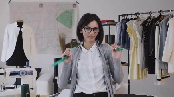 Portrét mladé ženy v práci, nosí brýle a při pohledu na fotoaparát. Detail módní návrhářka a švadlena úsměv na kameru v její stylový malý ateliér. Krásná holka v brýlích