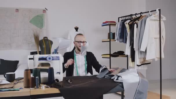 Kreative Designer und Schneider ist sitzen am Schreibtisch in seinem Design-Studio und verrückt über die Entwicklung einer neuen Kollektion. Atelier, verrückte Mode-Designer auf der Arbeit
