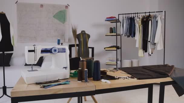 Stylové studio pro šití oblečení, které má šicí stroj, vinutá vlákna, různé šicí položky a textilie válí, panáky stojící a náčrtky připnul ke zdi, oblečení na ramínkách