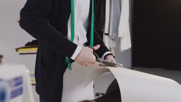 de22b00a1346d Jovem barbudo designer de moda com a linha de fita em seu pé pescoço na  studio de costura e corte com uma tesoura, um padrão para uma nova coleção.