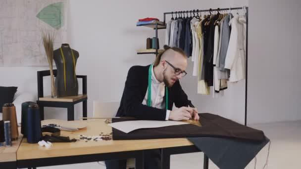 1cfd7da962da1 Jovem estilista desenhar esboços usando régua, cortar o pano para futuras  roupas com barba. Tecido, padrão e ferramentas de costura mentem sobre a  mesa de ...