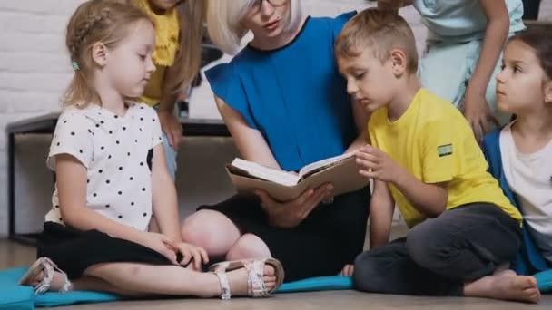 Kaukázusi tanár és a diákok ülnek egy kis párnák, olvasni egy könyvet együtt egy általános iskola vagy az iskolai osztályban. Olvasni egy történetet, hogy egy csoport elemi vagy általános iskolai tanár