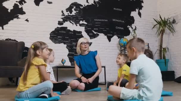 Group of kids sitting on the floor in circle around the teacher and studying geography in geography classroom. Cute little children with teacher in classroom at school