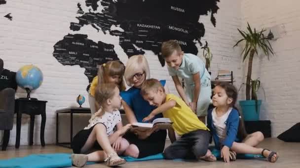 Grupo de niños hermosa hablando de libro con el maestro de cuarto de ...