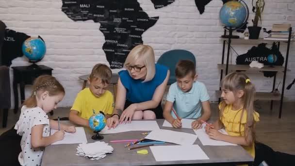 Základní škola krásné děti kreslení v učebně s učitelem pomoci. Děti kreslit výkres s učitelem ve třídě kreslení lekce