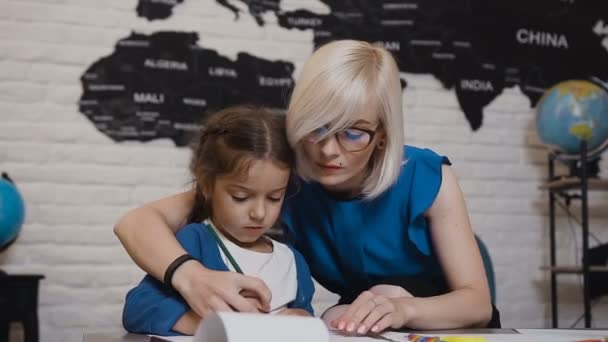 Mom teaches her daughter to write first letters. Teacher and student perform homework in elementary school. Young blonde teacher and her brunette little daughter sit at the desk in the classroom and