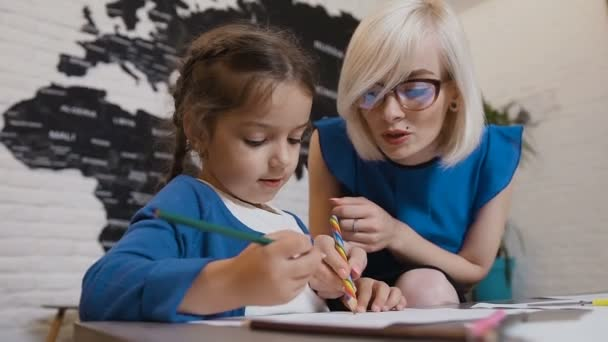 Cute teacher mom working with beautiful creative kid at elementary school. Teacher sitting at the desk next to a little girl as they writing homework together in classroom at elementary or primary