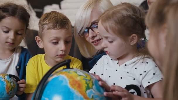 Close-up. Žena mladý učitel a studenti hledají zeměkoule s lupou v učebně zeměpisu. Roztomilý žáků a učitelů v učebně s koulí na základní škole