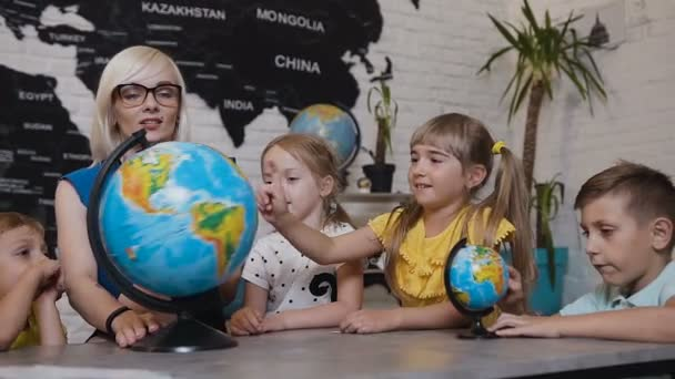 Beautiful pupils and teacher looks at globes in geography classroom on the lesson at the elementary school. Boys, girls and their young teacher study the map of the world using the globe and