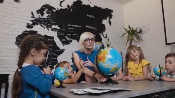 Učitel a děti diskusi globe v učebně zeměpisu na základní škole. Skupina rozkošný kavkazské studentů s učiteli se dívá na různých zemí světa a studie