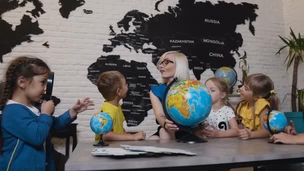 Učitel pomáhá školní děti v čtení globe v učebně zeměpisu na základní škole. Atraktivní učitel se vzdělávat jeho žáků na základní škole a použití zeměkoule aby je učili o