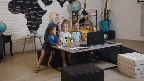 Female teacher with his small students fun watching laptop at geography class in primary school. Teacher and children using laptop in classroom