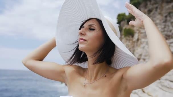 Portrét krásné mladé ženy v bílém plavkách a klobouku, pozadí moře modré vody a vrstvené skály. Koncepce: moře, slunce, cestování, dovolená, svoboda, těšit, letní