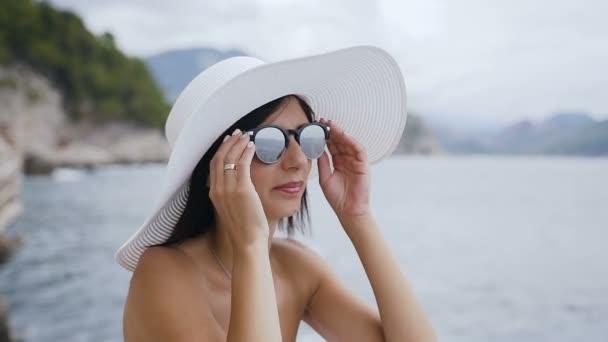 Portrét tváře dívka na dovolené. Roztomilá dívka v sluneční brýle a klobouk na pláži. Dovolená na moři. Letní dovolená