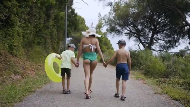 Rückseite. Mutter und ihr zweijähriger Sohn spazieren an einem sonnigen Sommertag durch den Park in Strandnähe. Eine junge Frau in Badeanzug und großem Hut geht mit Kindern in den Park am Meer.