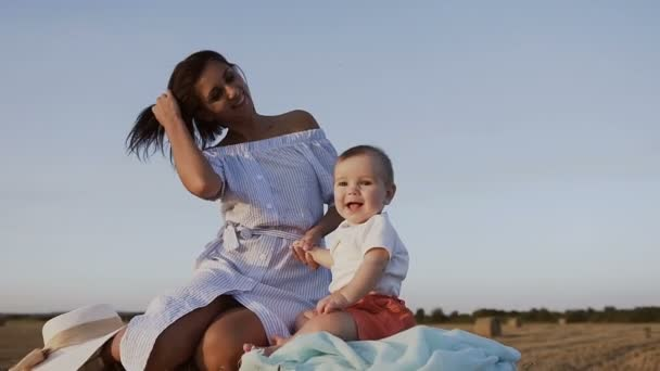 Portrait of a cheerful baby and his mother sitting on a bale with straw in the field. Young woman with her son walking outdoors in the field on a warm summer evening, slow motion