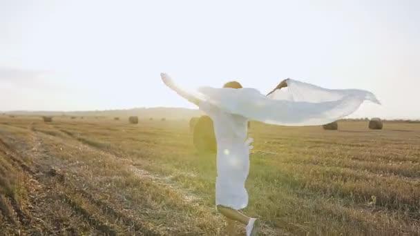 Pohled zezadu. Krásná dívka v dlouhých šatech baví venku v poli. Happy bruneta žena chůzi s šálou v poli s balíky slámy a užívání si přírody. Svoboda mladá atraktivní