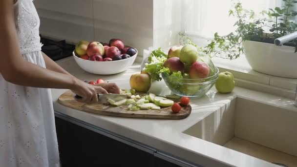 Ženské ruce nakrájí jablko na plátky pro ovocný salát na snídani v kuchyni ráno. Příprava ovocný salát. Zdravé stravování