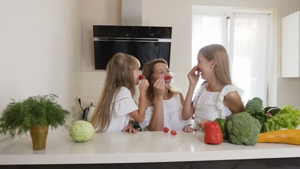 Two sisters and their mother are having fun with chili pepper at home in  the kitchen. The girls make a mustache with red pepper chili and show them  to each other. Fun family at kitchen, slow motion