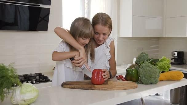 Dvě roztomilé sestry v bílých šatech vařit v kuchyni: dívky řezy papriky udělám salát. Starší sestra učí mladší sestru, aby snížení paprikou. Teen dívky připravit zeleninový salát doma v