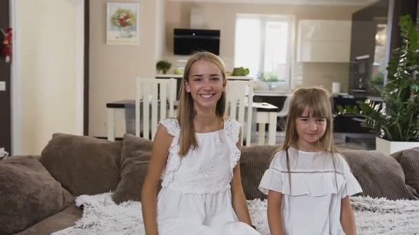 Lassított felvételeket a boldog két tizenéves testvér bed Room hotel essen. Szép, boldog lány az ágyon, nézi a kamerát, és esett vissza az ágyban otthon ül a fehér ruhák