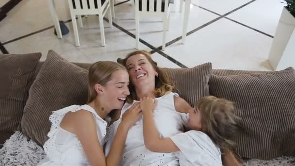 Dvě krásky a jejich krásná maminka doma baví. Roztomilé dívky s dlouhými vlasy v bílých šatech lechtání své milující matky, hnědý gauč mezi polštáře v moderním pokoji. Super