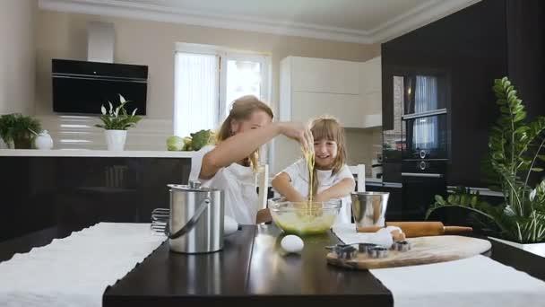 Jízda kamery šťastné úsměvy žena a malá holčička hnětení těsta společně ve velké skleněné mísy v kuchyni doma. Šťastná rodina v kuchyni. Matka a dítě Příprava těsta