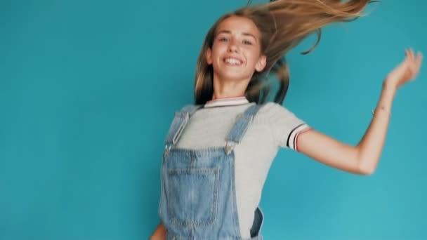 Happy vzrušená dívka s dlouhými vlasy vyskočit s rukama nad hlavou. Krásná dívka skoky a smích na štěstí. Portrét překvapující, šokován a skákání dívenky. Emoce, životní styl