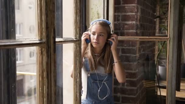 Portrét mladé atraktivní dívky na pozadí okna poslechu hudby pomocí sluchátek. Volný čas a relaxace v interiéru. Dospívající dívka se těší melodie v její sluchátka