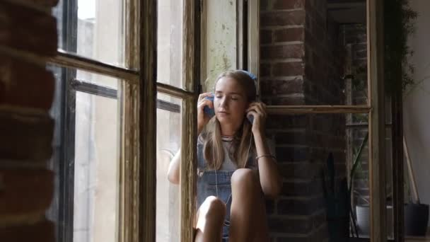 Portrait of young attractive girl on window background is listening to music with headphones. A beautiful teen girl sits near a window with headphones listening to music from smartphone