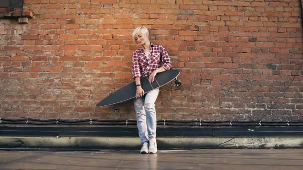Young blonde girl with longboard standing on the rooftop near red brick wall at sunset. Pretty blonde girl with longboard at the background of brick wall at rooftop the modern building