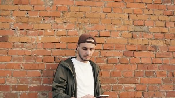 Young handsome man using smartphone in urban city background relaxing on brick wall. Happy hipster guy playing mobile games. Outdoors
