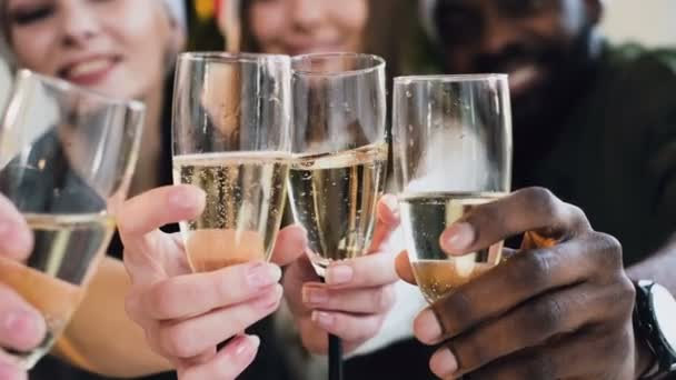 close-up the hands of people of different races who hold wine glasses of sparkling wine. bubbles in wine glasses with white wine against the background of beautiful guys and girls. The concept of