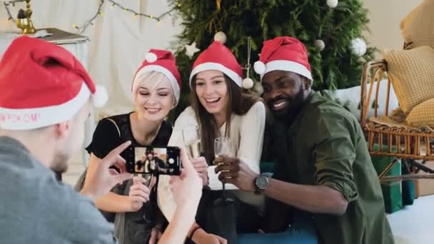 A group of people from different races posing and taking pictures on the phone. Cheerful friends in Santa hats make a photo on the smartphone at the christmas celebrate, good-looking young people