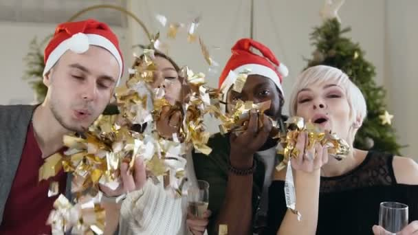 Detail. Čtyři veselé Smíšené rasy lidí vane zlaté konfety z rukou na vánoční oslavu nebo na nový rok. Pojetí večírku