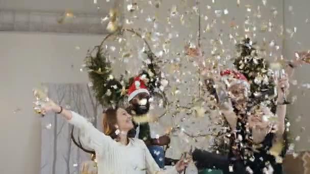 Gruppe junger Menschen feiern Weihnachten oder Silvester in der Wohnung einen Sekt trinken und viel Spaß mit gold Konfetti. Feier der Partei. Slow-motion