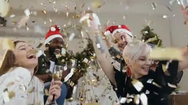 Giovani felici in vestiti festivi con bicchieri di vino sono sorridente e balli nel volano coriandoli oro sulla festa di Natale o Capodanno. Multi gruppo razziale della gente divertente che celebrano partito