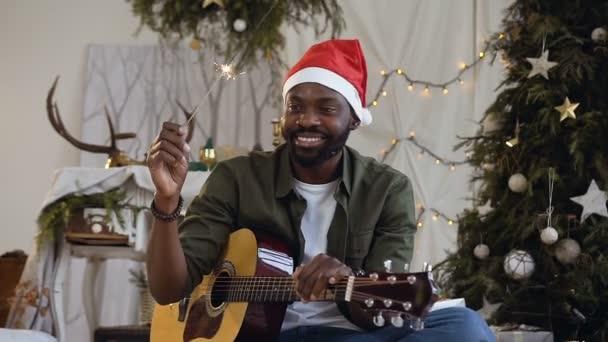 Usmívající se Afričan s kytarou a Bengálsko světlo sedí na podlaze v třpytivé zlaté konfety na pozadí vánoční stromeček. Koncept oslav nového roku, oslavy