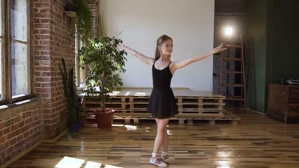 Okouzlující dospívající baletka v černém tutu trénovat taneční pohyby. Půvabná tanečnice v černém obleku provádí prvky klasického baletu