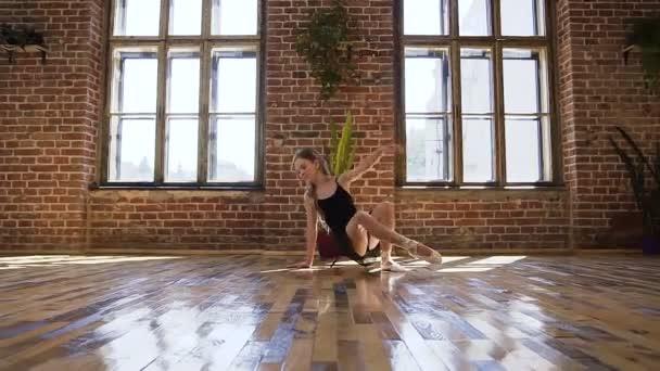 Elegantní baleríny provádí taneční skladba podlahy v tanečním sále. Mladý tanečník baletka provádí taneční umění v černé tutu a baletní boty na podlaze