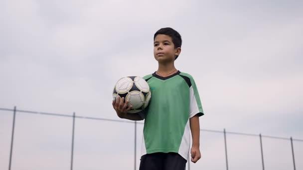 Portrét shot roztomilý chlapec kráčí s fotbalovým míčem.