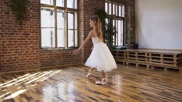 Professional, classic ballerina practices ballet moves in the modern class room ballet school. Graceful beautiful ballerina dressed in white tutu dancing gracefully on her pointe ballet shoes